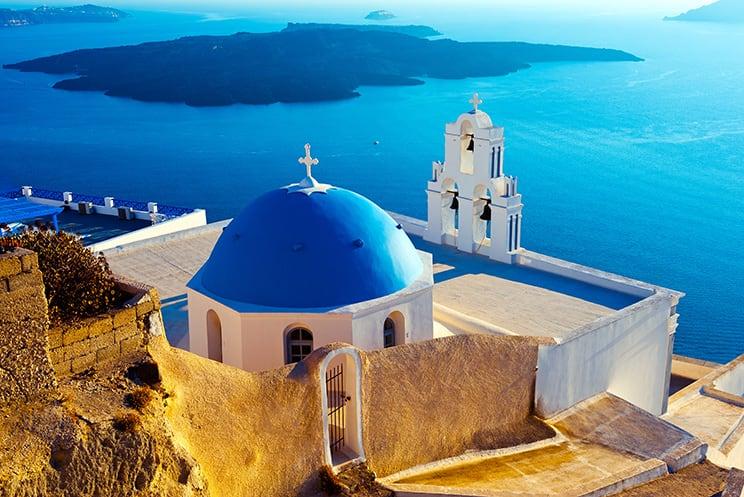 Santorini blue domed church on the coastline