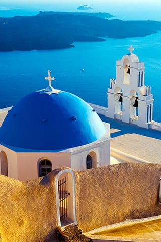 Waterfront blue domed church in Santorini overlooking greek island