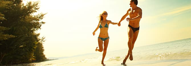 A Couple Running Beachside Enjoying the Sun and Cool Breeze