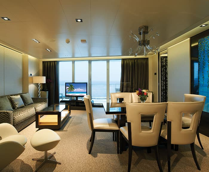 Sala de estar de The Haven's Deluxe Owners Suite con balcón grande en el Norwegian Getaway