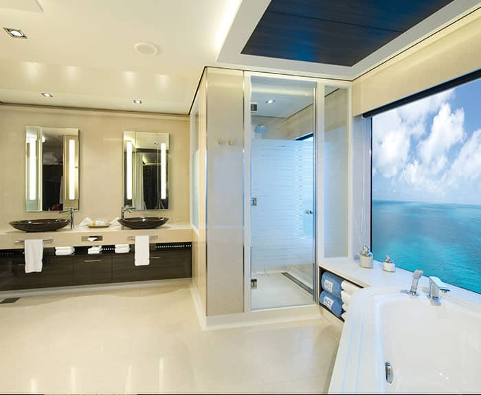 Banheiro da Deluxe Owner's Suite com varanda grande do The Haven no Norwegian Getaway
