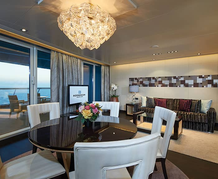 Sala de estar da Deluxe Owner's Suite com varanda grande do The Haven no Norwegian Escape