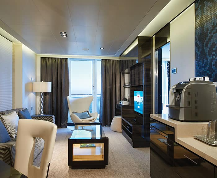 Sala de estar de The Haven's Owners Suite con balcón grande en el Norwegian Breakaway