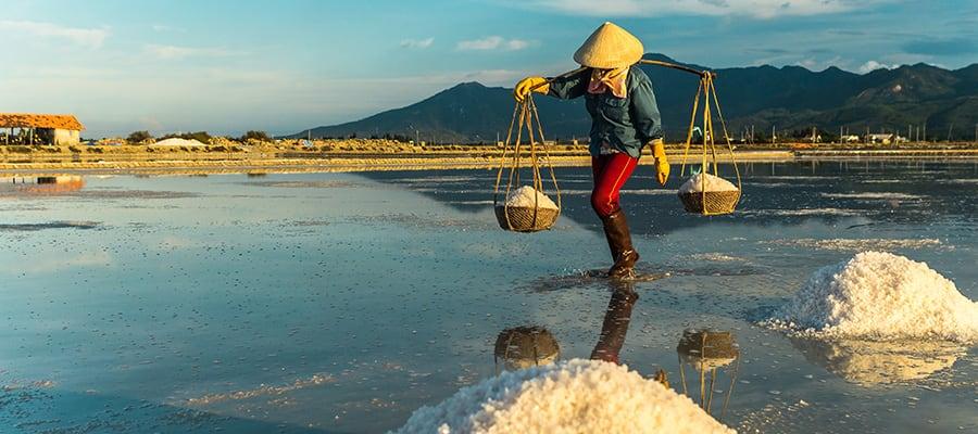 Mujer llevando sal de una granja de sal en Nha Trang