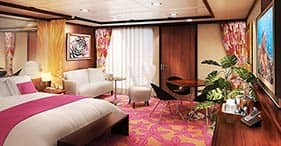 Norwegian Pearl cruise ship Penthouse with queen-sized bed, dining area, and pri