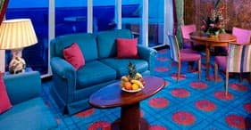 Norwegian Sky cruise ship Owner's Suite with queen-sized bed, dining room, and p